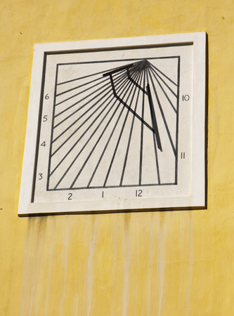 sun dial: An old-fashioned sun dial on a stained yellow wall on the kat, or command building, in the Castle of Good Hope in Capetown, South Africa. As marked, using the shadow lines, it keeps time from 10am to 6pm. Stock Photo