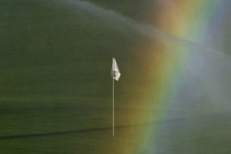 A golf course rainbow resulting from sunlight being diffracted through spray from the sprinkler system. While artificially created, the effect is quite pretty. 版權商用圖片
