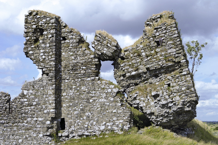 tilting: The ruined facade of Clonmacnoise Castle in County Offaly, Ireland. The ruins show elements of the old stone walls tilting on a little knoll or hill in the country. Stock Photo