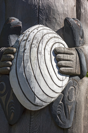 A small detail from a carved wooden totem pole showing two sea otters holding a large clam. photo