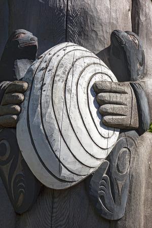 totem indien: Un petit détail d'un totem en bois sculpté montrant deux loutres de mer tenant un grand palourdes.