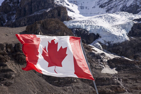 canadian flag: The maple leaf of the Canadian Flag flutters in a brisk wind. In the background, the main glacier of Mount Andromeda tumbles from the summit headwall.