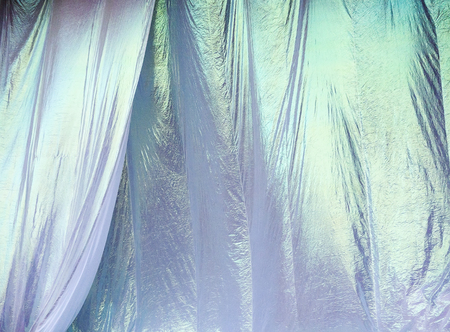 Irridescent white curtains ripple and billow in a light breeze before being pulled down at an outdoor concert.