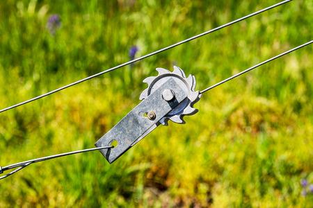 녹색 배경 와이어 울타리의 긴장을 증가하는 데 사용되는 와이어 장력 장치.