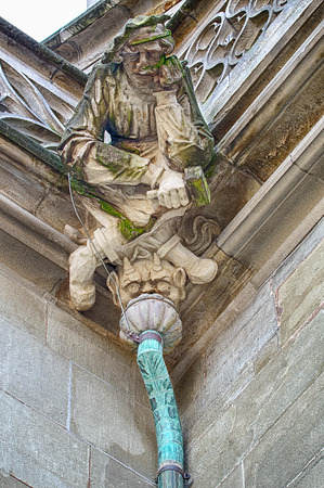 gargoyle: Bern, Switzerland - November 23, 2014: A detailed figure of a stonemason carved in stone sits over a demon on top of one of the drains on the Bern Minster Cathedral in Switzerland. Editorial