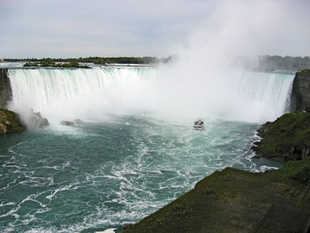 niagara river: A view of Horseshoe Falls -- the Canadian side of Niagara Falls. In the river in the foreground is the boat that takes tourists into the mist under the falls. Stock Photo