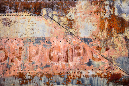 rust covered: A side panel of an old railroad car is covered with rust, peeling paint, and old rivets in a post-industrial abstract background. Stock Photo