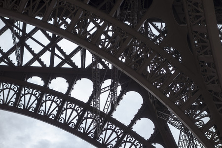 ironwork: A detail view of a portion of one of the base arches on the Eiffel tower that shows details of the art deco ironwork silhouetted against a cloudy sky..