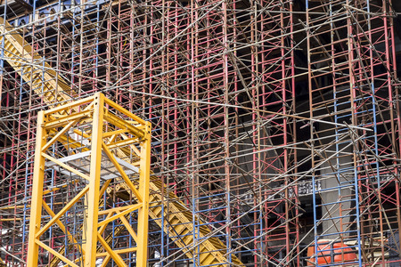 Construction background showing scaffolding on a construction site with a yellow trash chute running diagonally through the complexity.
