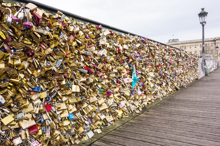 meant to be: PARIS, FRANCE - NOVEMBER 28., 2014:  Lovers have locked thousands of locks to the railing of the Pont des Arts bridge in Paris. The padlocks, with keys thrown into the Seine River, are meant to be symbols of everlasting love and is a modern tradition that