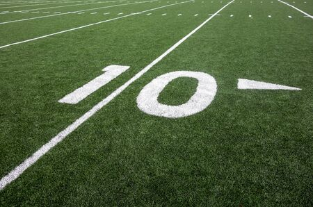 Markings for the ten yard line on an American football field indicate the distance to the goal line.