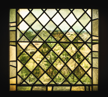 distort: An old stained glass window with pigmented window panes and leaded glass distorts the French countryside into a a view that looks like an impressionist painting.
