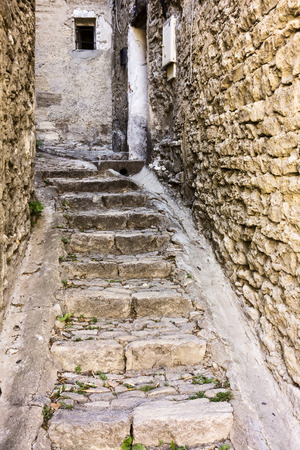 gordes: A narrow alley in Gordes in Provence France has just enough space for steps and two small gutters as it winds between buildings.