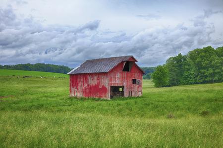 Een klassieke rode schuur staat in de grasrijke heuvels van een boerderij in Oost-Ohio.