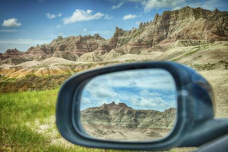 rearview: A mountain range of the colored hills as viewed through the rearview mirror window of a car by the roadside in Badlands National Park in South Dakota.