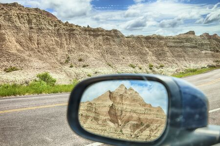 A small mountain viewed through the rearview mirror window of a car by the roadside in Badlands National Park in South Dakota.