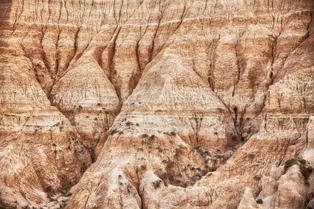 A detailed view of the erosion shaping the hills of the Badlands National Park in South Dakota.