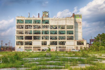 abandoned factory: An old factory  in the Highland Park area shows the postindustrial plight of Detroit with broken windows and a parking lot filled with weeds. Stock Photo