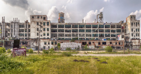 buildings on water: DETROIT USA  JUNE 9 2015: The Fisher Body Plant is now shut down and covered in graffiti but was used in automotive manufacturing from 1919 until 1984. The building was designed by Albert Kahn and built in 1919.