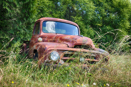 rusting: WALDRON USA  JUNE 18 2015: A frontal view of an old International Harvvester truck that is slowly rusting on a farm on Waldron Island shows the front grill hood and insignia on the grille. Editorial