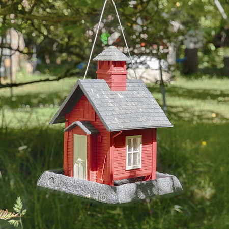 schoolhouse: A small feeder in the form of a schoolhouse is hung from a tree just outside a oneroom schoolhouse. Stock Photo