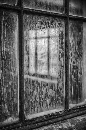 windowpane: An architectural abstract image where two windows are visible. One window is barely visible through a second dirtstained window. In black and white. Stock Photo