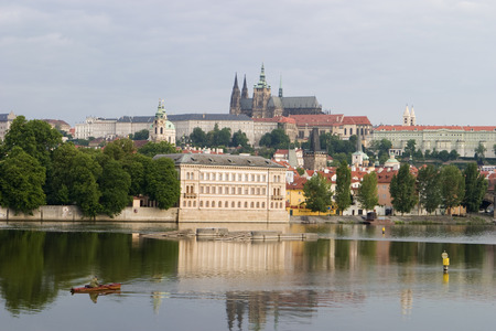 vltava river: A single man rowing up the Vltava River in Prague with the Prague castle and cathedral in the background. Editorial