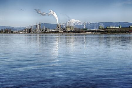 mt baker: ANACORTES USA  JANUARY 26 2015: Of two oil refineries in Anacortes Washington emits steam with a snowcovered Mt. Baker in the background.
