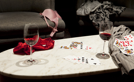 strip shirt: The outcome of a game of strip poker with womens clothing strewn over a chair and table and a mans shirt on the right side.Two partly full glasses of wine are also on the table.