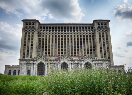 disrepair: DETROIT, USA - JUNE 9, 2015: A view of the front facade of the Michigan Central Railway Station as seen over weeds growing in front of the building. The historic landmark is in disrepair. Editorial