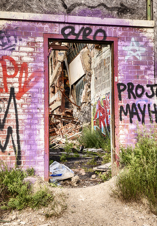 urban decay: DETROIT, USA - JUNE 12, 2015: A graffiti painted doorway at the old Fisher Body Works Factory shows some of the decayed remains of the old automotive factory.