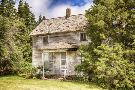 An old Iowa farmhouse is slowly decaying although the lawn and landscaping are being maintained. Stock Photo