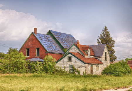 urban decay: DETROIT, USA - JUNE 9, 2015: An abandoned with broken windows house located next to an empty lot full of weeds  symbolizes urban decay in post-industrilal Detroit.
