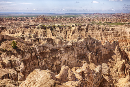 hing: A view of the Pinnacles portion of Badlands National Park in South Dakota showcases the erosion within the hills with just a hing of the grasslands in the distance. Stock Photo