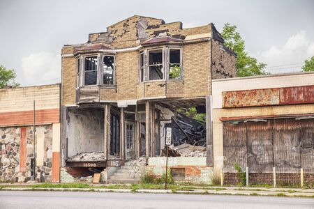 burned out: DETROIT, USA - JUNE 9, 2015: A burned out and semi-demolished building between two closed storefronts on Hamilton Avenue in Detroit, Michigan is symbolic of the urban blight that is emblematic of the city. Editorial