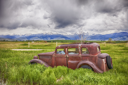 rusts: An old car rusts away on a farm near Harrison, Montana with the Tobacco Root Mountains in the background. Stock Photo