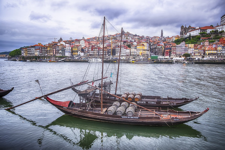 PORTO, PORTUGAL - MAY 2, 2015: Two boats filled with pipes, or barrels, of port wine are floating on the Douro River with the city of Porto rising up on the hills in the background. The boats carry the names of the port houses as floating ads.