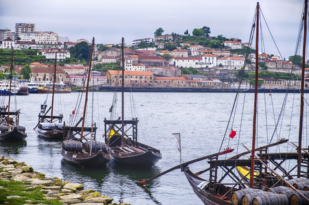transported: A fleet of boats are lined up against the banks of the Douro River in Porto, Portugal. Historically, these boats transported the barrels, or pipes, of port wine from the vineyards to the wineries in the city of Porto.