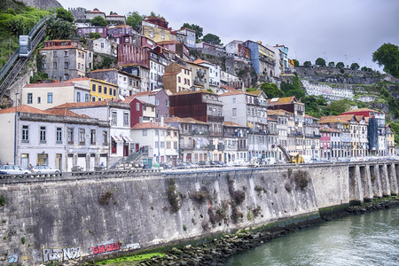 hillsides: Buildings climb the steep hillsides of the Douro River in the city of Porto in Portugal. A funicular is visible in the upper left as it climbs the hill. Editorial