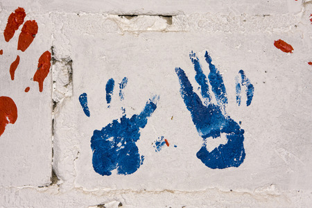 handprints: A pair of blue and red handprints on a white concrete wall make a colorful display on a preschool wall in a township in South Africa.