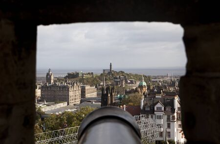 edinburgh background: A view of Edinburgh framed through one of the rough stone gunports of Edinburgh Castle. The Old City is in the foreground and parts of the New City and Calton Hill are in the background.