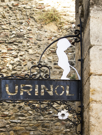 public figure: A humorous sign for a public urinal in the Castelo barrio of Lisbon, Portugal illustrates a cutout figure of a boy taking appropriate action.