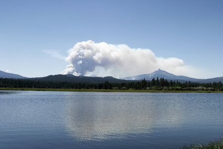 oregon cascades: A cloud of smoke rises from the Lake George forest fire in Central Oregon in 2006.  The plume of smoke is rising over Mt. Washington in the Oregon Cascades. Stock Photo
