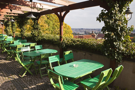 seating area: The outdoor seating area with green tables and chairs in a restaurant near the Prague Castle in the Czech Republic. In the background are the roofs of the Old Town.