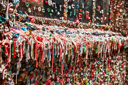 pike place: The landmark bubble gum wall near the Pike Place Market in Seattle is a dirty, unhygienic wall filled with half-chewed bubble gum that is dripping from every surface.