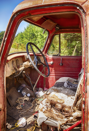 The interior of an old red truck shows the wear and tear of years of neglect including the box springs and stuffing of the seat and exposed wires.