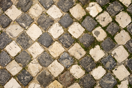 alternating: A cobblestone sidewalk in the Alfama neighhborhood of Lisbon has arranged the light and dark stones in an alternating pattern like a checkboard.