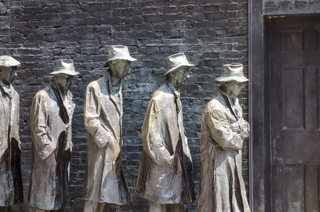 WASHINGTON DC, USA - AUGUST 20, 2014: An art installation at the Franklin Delano Roosevelt Memorial in Washington DC shows a bread line of five men waiting at a door to commemmorate the Great Depression of the 1930s.