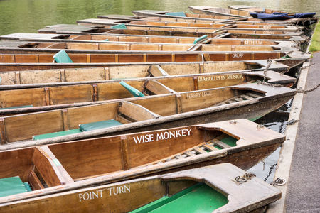destination scenics: CAMBRIDGE, ENGLAND - MAY 9, 2015:  Flat bottom boats, or punts, with colorful names are commonly used to transport tourists along the River Cam in Cambridge, England.