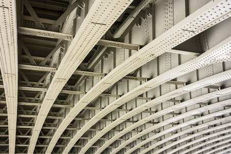 girders: The underside of a bridge in London shows the architectural details of a geometric pattern of curved beams and girders that provide infrastructre support for the road abovve.